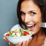 Woman holding bowl of salad against blue background