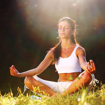 yoga woman on green grass lotus pose in sunrise light